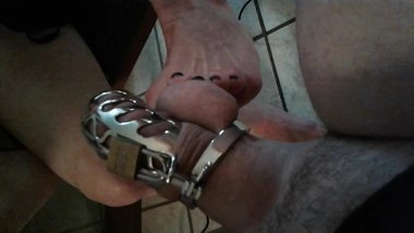 AprilShowers17 teasing his caged cock with my feet :-)